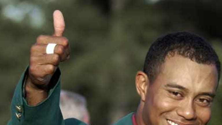He's back ... in this April 14, 2002, file photo, Tiger Woods, wearing his green jacket, gives a thumbs up as he celebrates winning the Masters golf tournament at the Augusta National Golf Club in Augusta.