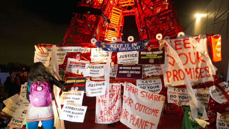 A participant puts posters on the mini red Eiffel Tower as NGO representatives staged a sit-in protest in Paris.