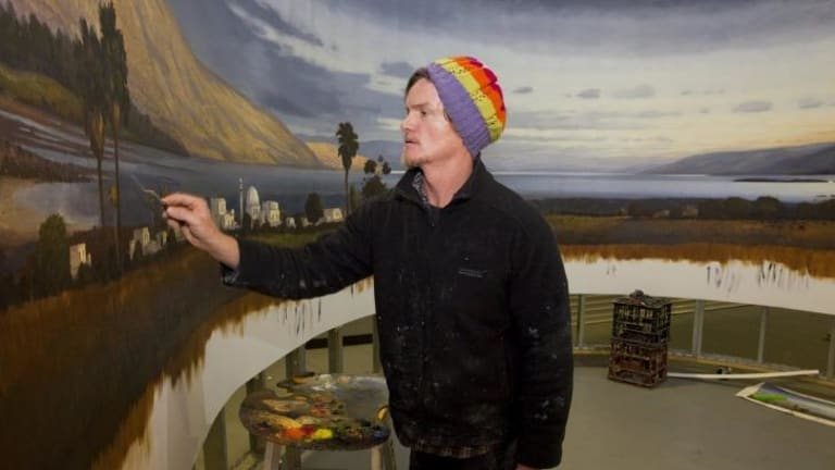 Painting in the round: Alexander McKenzie at work in a Canberra hangar.