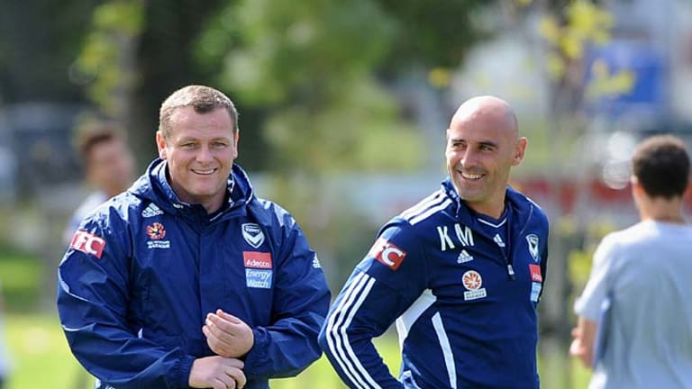 Having a laugh: Jim Magilton and assistant Kevin Muscat direct Victory's preparation for Friday's match against Adelaide.