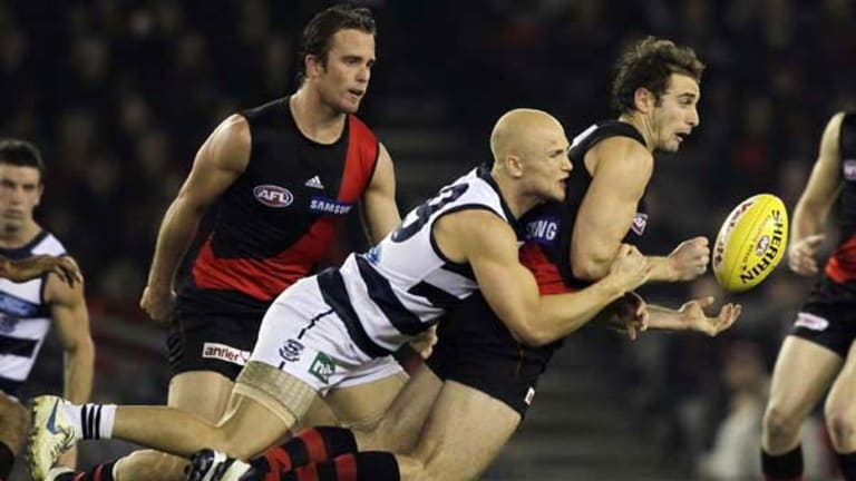 Gary Ablett wraps up Essendon skipper Jobe Watson during the Cats' thorough demolition of the Bombers at Etihad Stadium last night.