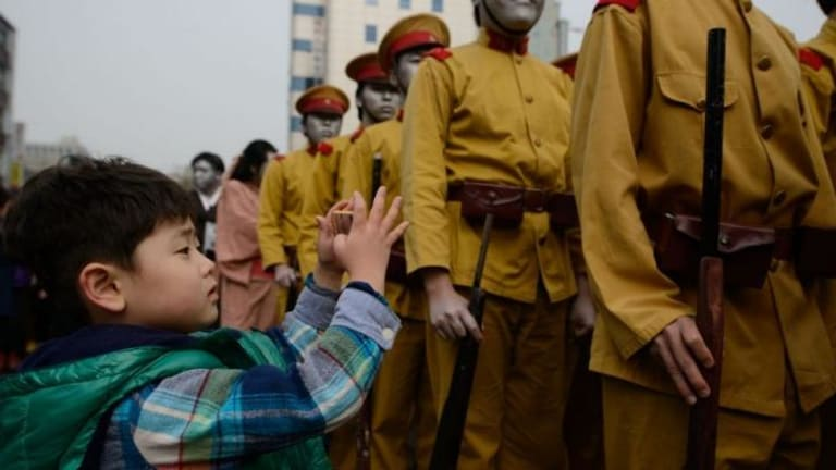 A boy in South Korea takes photos of activists dressed as colonial-era Japanese soldiers prior to their re-enactment of a crackdown in which hundreds of protesters were killed in 1919 during demonstrations calling for independence from Japan.