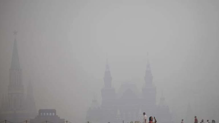 A tourist takes pictures at Red Square in a thick blanket of smog.