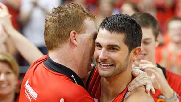 Wildcats' newest star Kevin Lisch is embraced by coach Rob Beveridge after winning the NBL championship in Perth last night.
