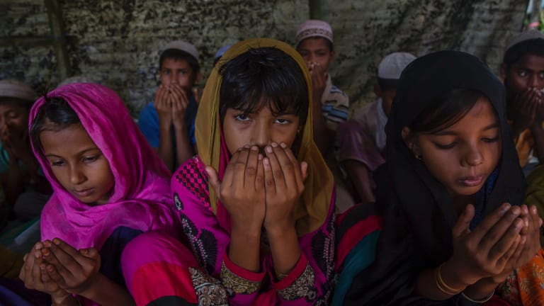 Rohingya Muslim girls, who crossed over from Myanmar into Bangladesh, pray at the end of their Quranic lesson in a newly opened madrasa, or religious school, at Kutupalong refugee camp, Bangladesh on Sunday.