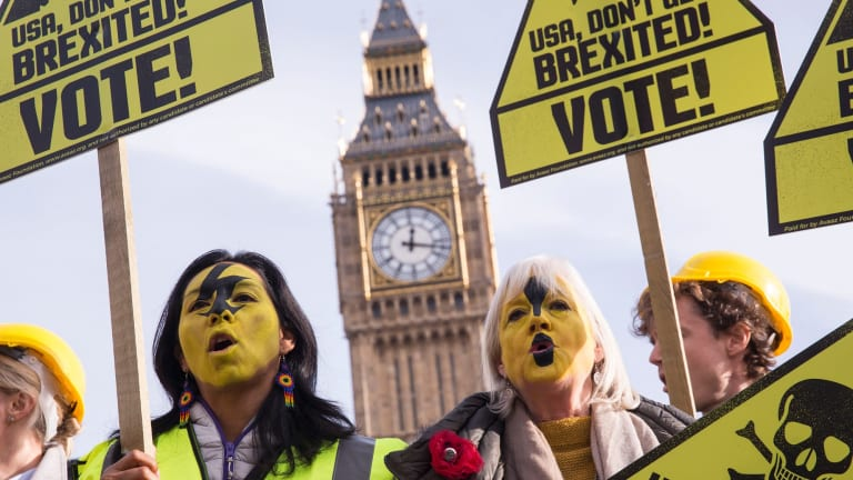 Demonstrators, organised by the civic movement AVAAZ in London, hold placards calling on Americans to vote and avoid getting 'Brexited'.