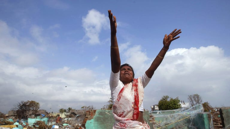 A local fisherwoman gestures for assistance to a hovering navy helicopter in the southern Indian state of Tamil Nadu after the boxing day Tsunami in 2004.