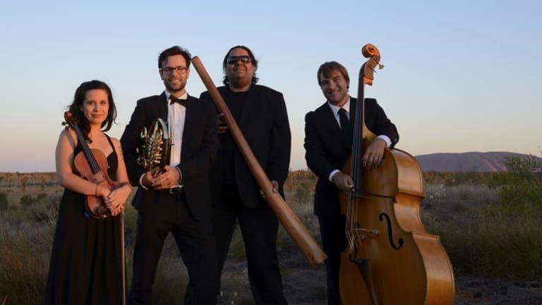Didgeridoo player William Barton and members of the Darwin Symphony Orchestra at Uluru.