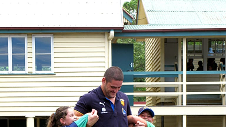 The Lion and the cubs ... Brendan Fevola plays with Sunshine Coast students.