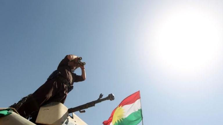 A Peshmerga fighter monitors the area in Bashiqa, near Mosul.
