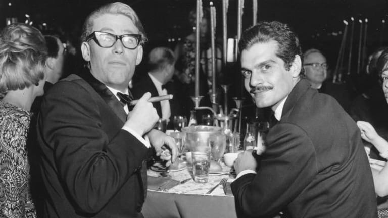 Peter O'Toole, smoking a cigar, and Omar Sharif have dinner after the premiere of <i>Lawrence of Arabia</i> in 1962.