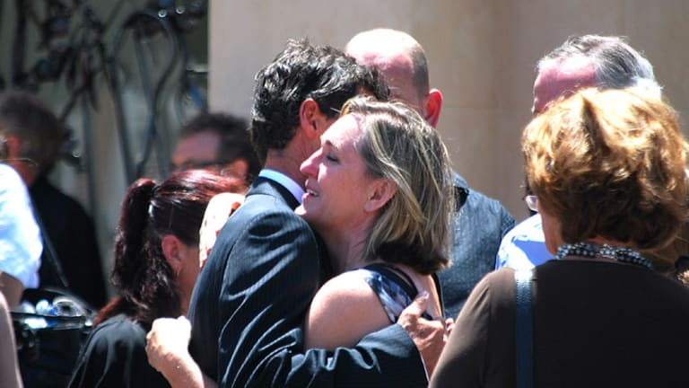 Harley Cuzens is consoled by a friend outside the memorial service for his two young daughters.