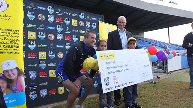 Freshly shaven Bulldogs Coach Des Hasler presented a $100,000 cheque to Camp Quality earlier this year.