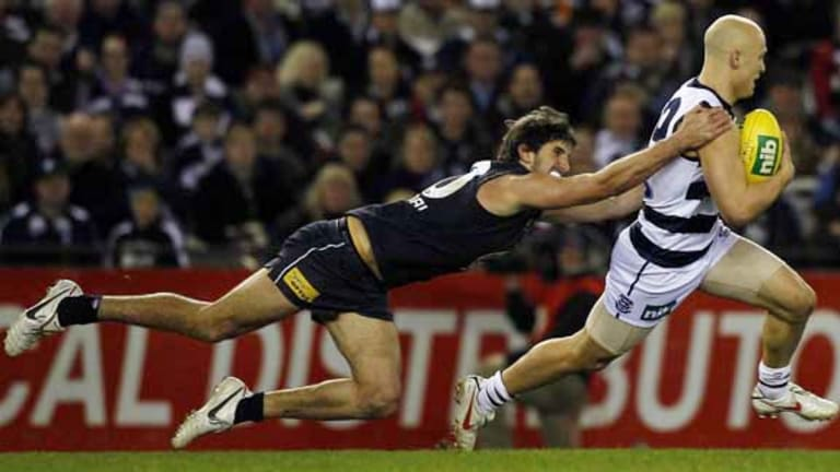 Gary Ablett puts on the pace to evade a desperate tackle from Jarrad Waite in Geelong's 42-point win last night.