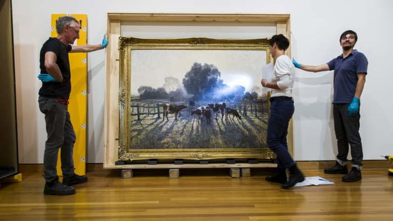 <em>Spring Frost</em> by Elioth Gruner is hung at the Canberra Museum and Gallery while Melissa Harvey inspects the work for any damage.