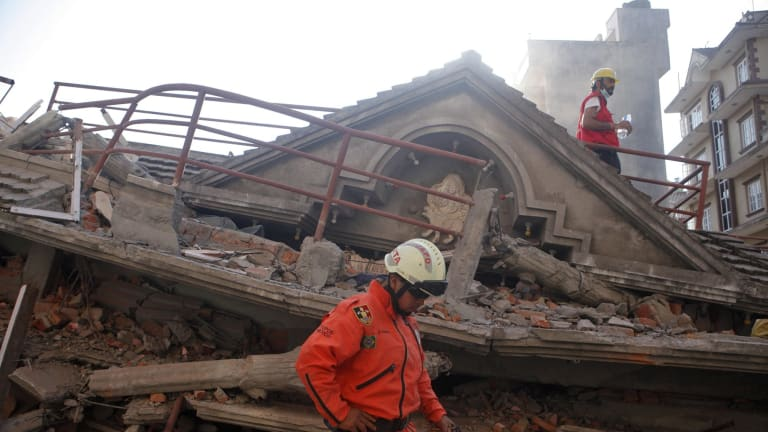 A Mexican rescue worker stands at the site of a building that collapsed in a second earthquake in Kathmandu, Nepal.