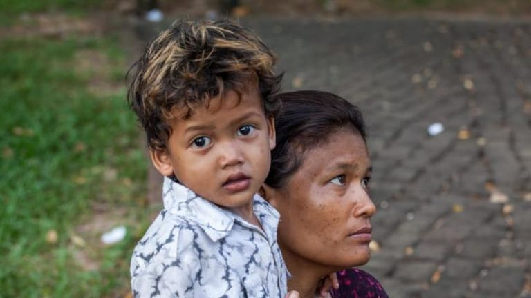 Srey Kuoch, a sex worker and drug user, hugs her young son, Chan Vutha, in Wat Phnom Park, opposite the residence of the Australian ambassador.