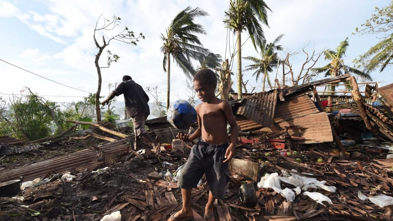 Grim aftermath: A child walks through the ruins of his family home with his father Phillip, on March 16 in Port Vila and, below, more scenes of the devastation in Vanuatu.