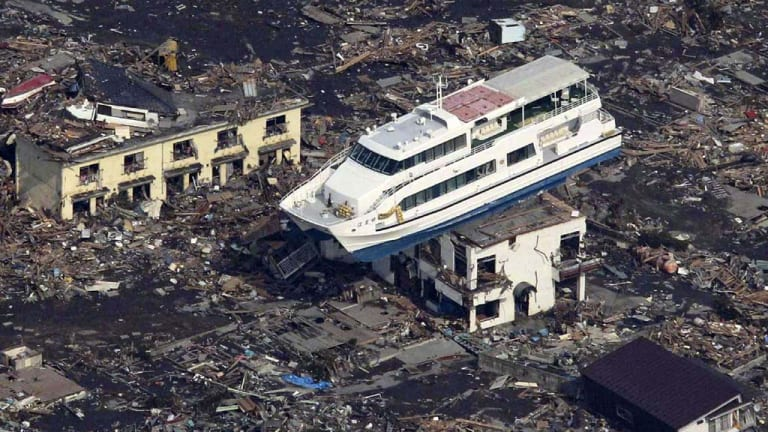 This aerial shot shows a pleasure boat sitting on top of a building amid a sea of debris in Otsuchi town in Iwate prefecture today.
