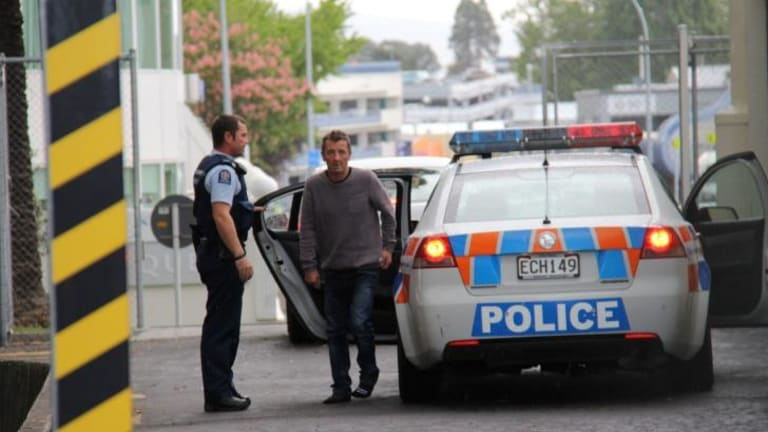 Police custody ... Phil Rudd, 60, dressed in jeans and a grey sweater.