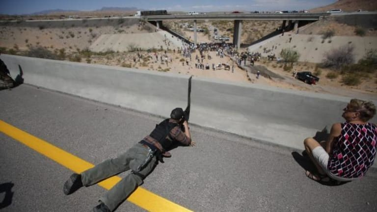 Eric Parker from central Idaho aims his weapon from a bridge as protesters gather by the Bureau of Land Management's base camp.