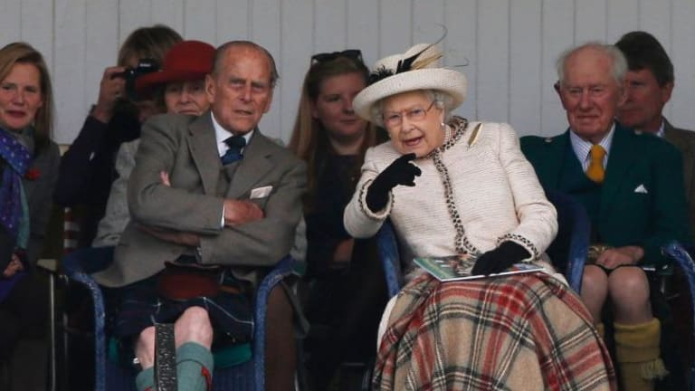 Queen Elizabeth and Prince Philip watch the caber being tossed at the annual Braemar Highland Gathering in Braemar, Scotland.