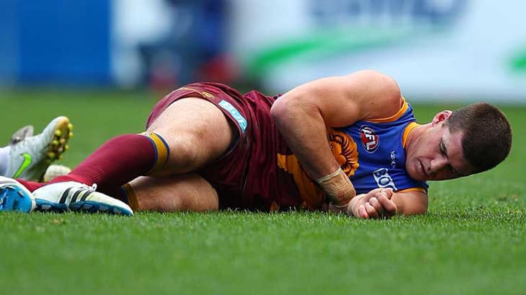Injured Brisbane Lions skipper Jonathan Brown sprawls on the ground in the game against Geelong at the Gabba.