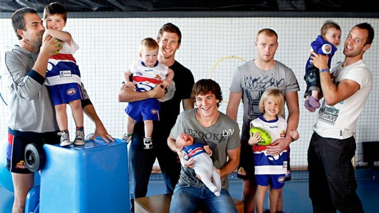 Western Bulldogs players with their young sons, from left, Brian Lake with three-year-old Cohen, Dale Morris with two-year-old Riley, Liam Picken with four-week-old Malachy, Adam Cooney with three-year-old Jaxon and Daniel Cross with 15-week-old Tyler.