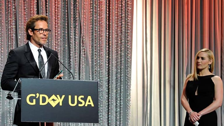 Actor Guy Pearce accepts the award for Excellence in Film & Television, presented by actress Kate Winslet.