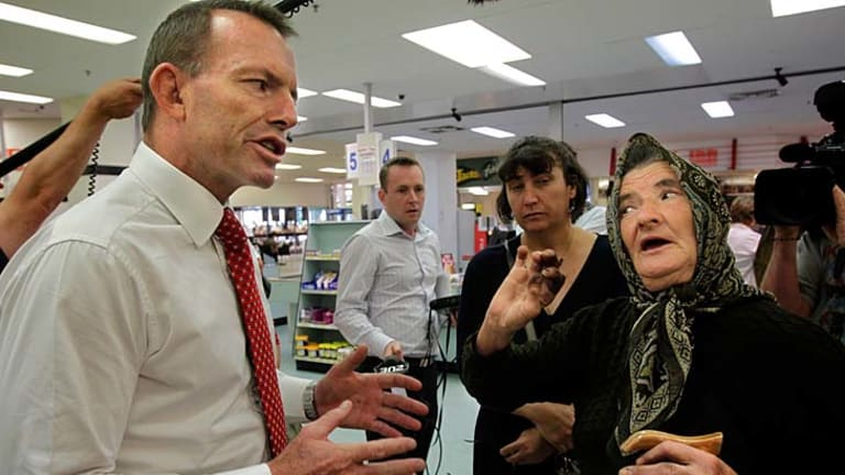 Tony Abbott (left) speaks to constituents.