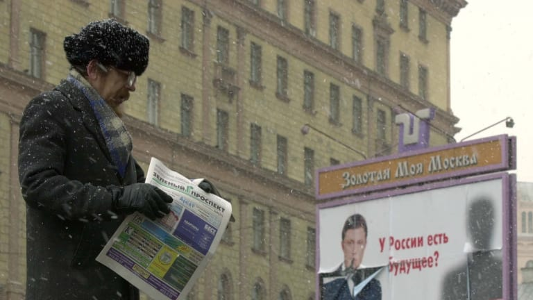 A man hands out free advertising newspapers in Moscow while behind him looms the Federal Security Service building. The Federal Security Service is the former KGB.