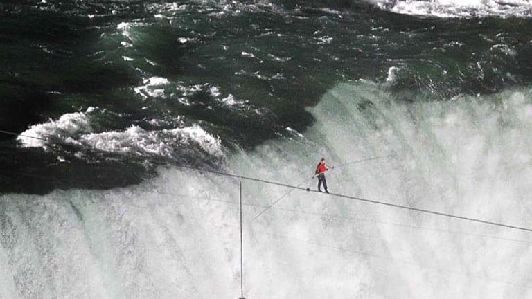 Tightrope walker Nik Wallenda avoids the dangerous plunge below and safely crosses Niagra Falls.