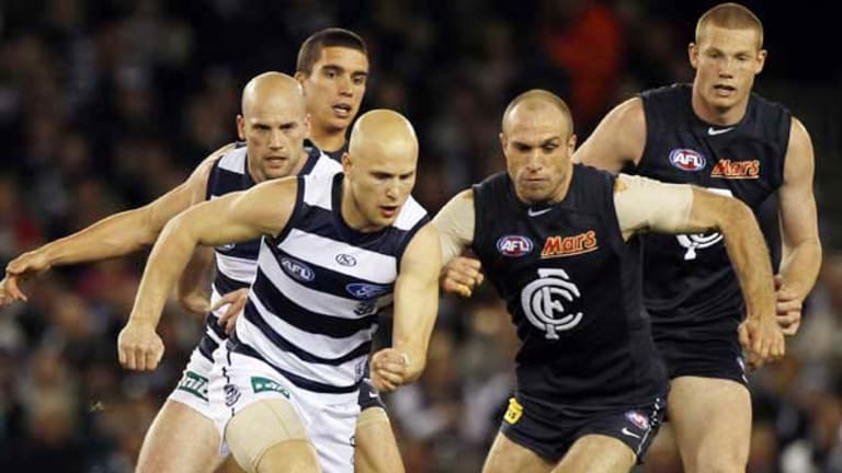 Superstars Ablett and Chris Judd contest a loose ball.