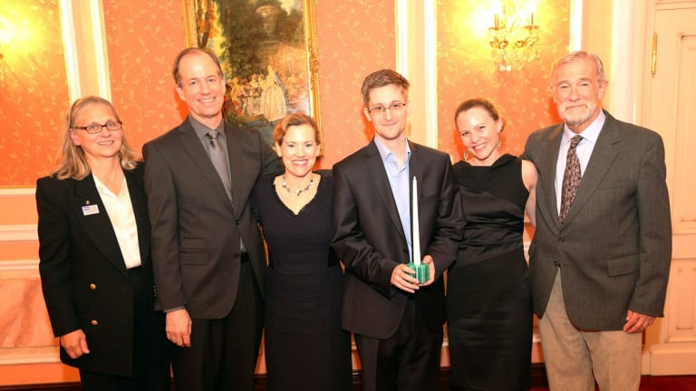 Snowden receiving the Sam Adams Associates for Integrity in Intelligence Award (SAAII) alongside UK WikiLeaks journalist Sarah Harrison (second from right) who took Snowden from Hong Kong to Moscow and obtained his asylum, and the United States government whistleblowers who presented the award, Coleen Rowley (FBI), Thomas Drake (NSA), Jesselyn Raddack (Department of Justice) and Ray McGovern (CIA) in October 2013 in Russia.