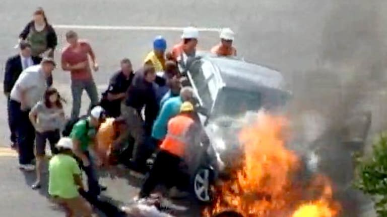 Bystanders brave the threat of an explosion as they lift the flaming BMW to rescue an injured motorcyclist.