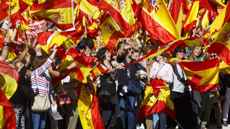 Demonstrators in Madrid hoist Spanish national flags in support of unity between Spain and Catalonia.
