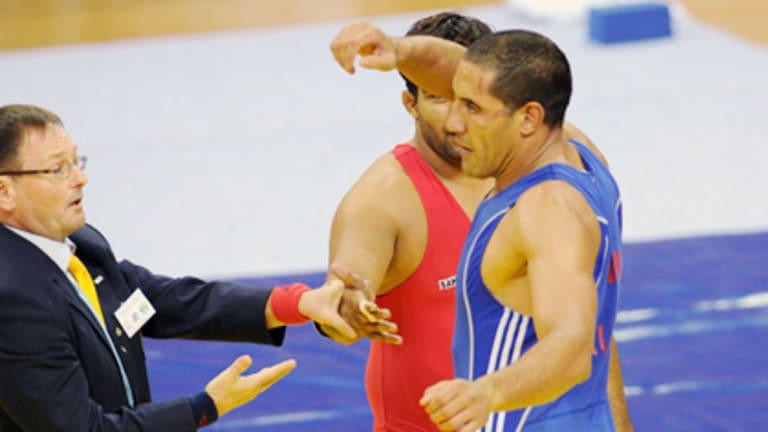 Australian wrestler Hassene Fkiri refuses to shake hands with India's Anil Kumar (obscured).