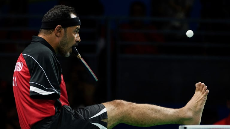 Hamadtou flicks the ball up with his toes to serve.