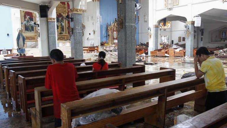 Residents pray inside a damaged Catholic Church after super Typhoon Haiyan battered Tacloban city.