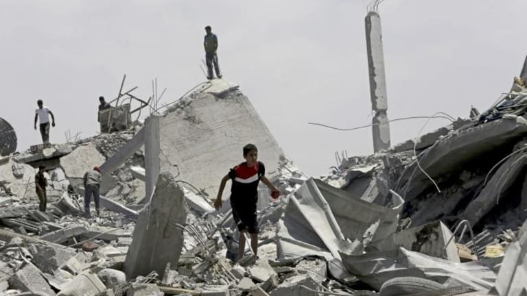 Palestinians search the rubble of homes in Khuza'a.