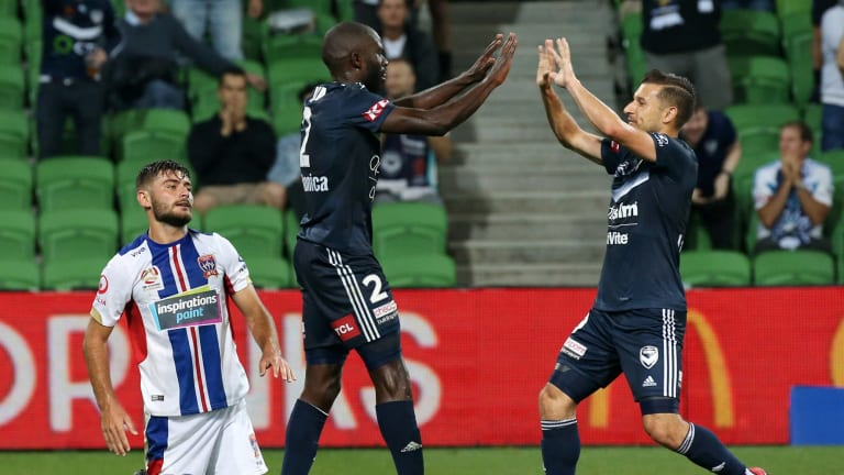 Victory's Jason Geria celebrates winning the penalty with Kosta Barbarouses after he was tripped by Newcastle's Ivan Vujica.
