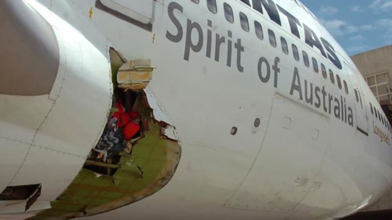 Qantas pilot Captain John Francis Bartles inspects the hole in the fuselage.