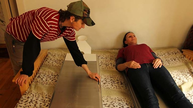 Quality control ... Victoria Spence, above right, tries out one of the cooling beds which allow a body to be kept in the home for up to five days.