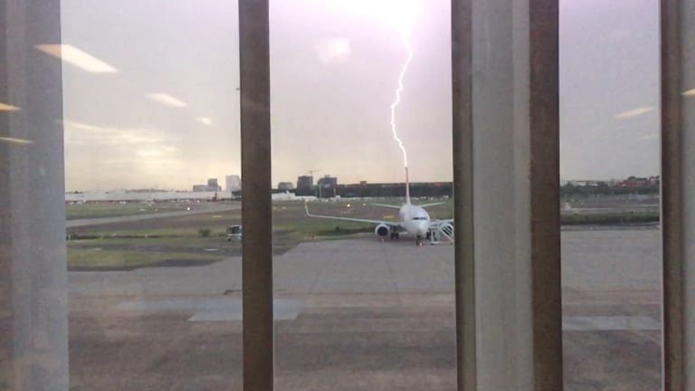 Lightning appears to strike the tail of a Qantas Boeing 737 aircraft at Sydney Airport on Thursday.