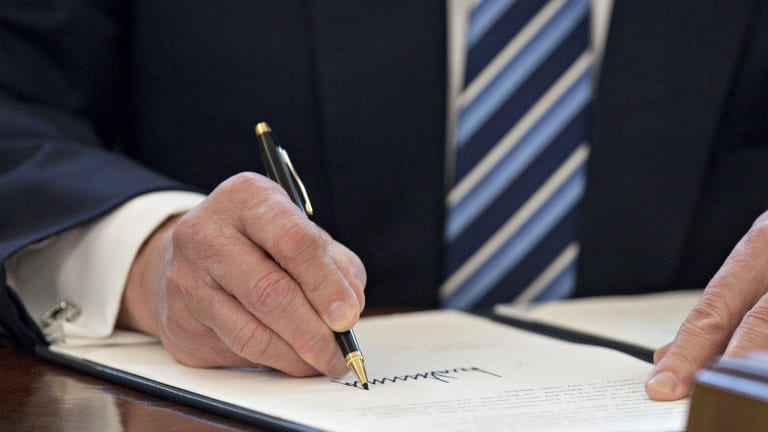 Donald Trump signs an executive order in the Oval Office.
