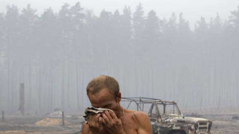 Alexander, 50, wipes his face in front of a charred car during a fire at the village of Peredeltsy that was burned to the ground by a wildfire in Ryazan region. <i>Picture: AP/Sergey Ponomarev</i>