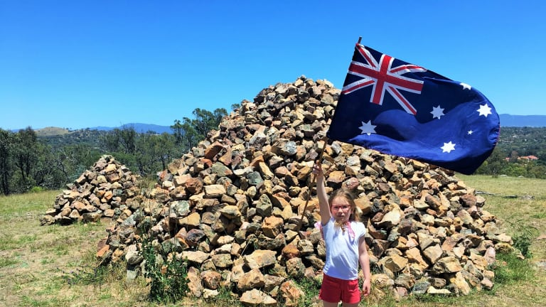 Emily flies the Australia flag at the mystery rock cairns atop Gossan Hill.