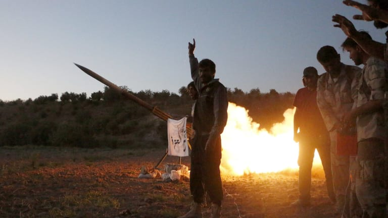 Tajammu Al-Ezza brigade fighters fire a shell towards the forces of Syria's President Bashar al-Assad stationed at Salhab village, in the Hama countryside on Friday.