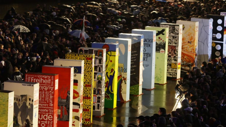 Twenty years on ... people crowd the individually painted dominos along the former route of the Berlin Wall.