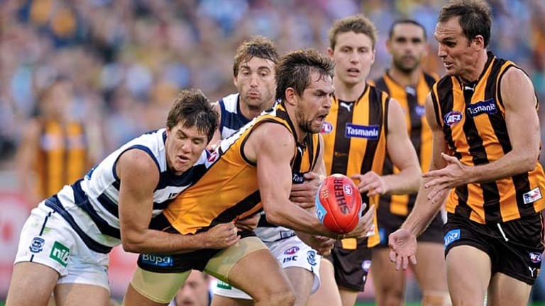 Luke Hodge is tackled by Andrew Mackie during the round 5 clash between Hawthorn and Geelong.